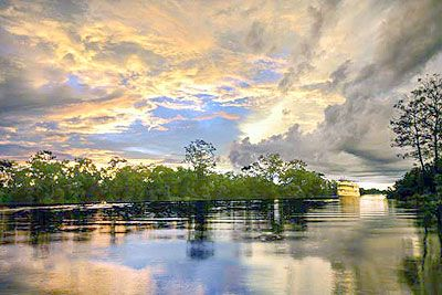 Amazon Sunset with the Motor Yacht Tucano upstream on the river.